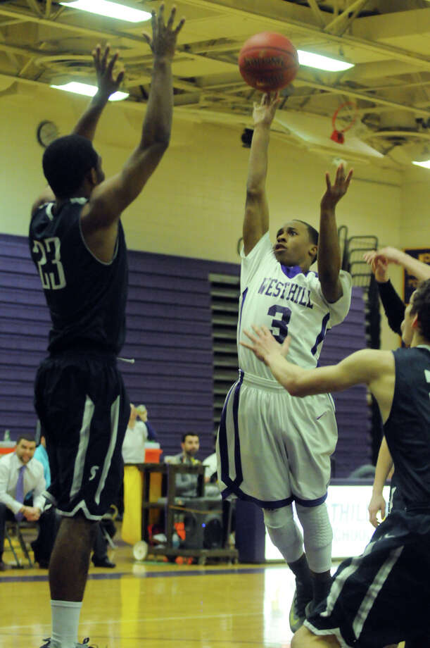 Westhill's CJ Donaldson shoots as Darryle Wiggins blocks as Westhill High School hosts Staples in a boys basketball game in Stamford, Conn., Feb. 19, 2014. Photo: Keelin Daly / Stamford Advocate Freelance