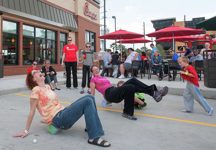 "Mari Ann Wise, left, and her friend, Robin Allen, right, participate in a dance competition before the opening of a Chick-fil-A restaurant on Briar Forest near Eldridge Pkwy S,  Wednesday, Feb. 19, 2014, in Houston. Chik-fil-A put together activities to entertain the early arrivers as well as fed them three times on Wednesday. The first 100 adults in line will receive a free year's supply of Chick-fil-A meals. ""I just wanted to experience it,"" Wise said. ""You only live once."" Photo: Cody Duty, Houston Chronicle / © 2014 Houston Chronicle"