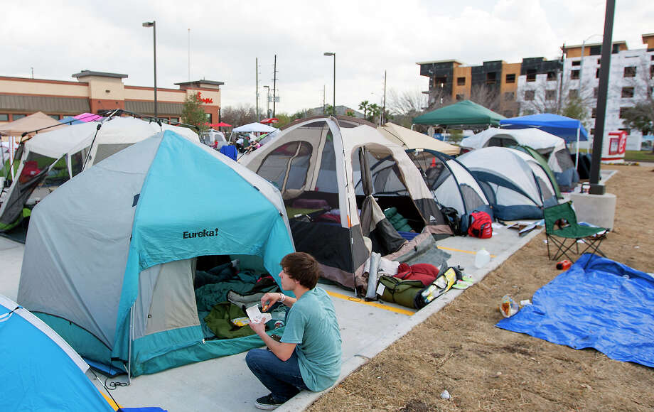 Tanner Plante eats outside his tent as he waits for the opening of a Chick-fil-A restaurant on Briar Forest near Eldridge Pkwy S,  Wednesday, Feb. 19, 2014, in Houston. Campers arrived with tents as the first 100 adults in line will receive a free year's supply of Chick-fil-A meals. Photo: Cody Duty, Houston Chronicle / © 2014 Houston Chronicle