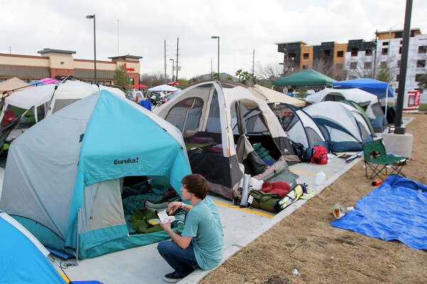 Tanner Plante eats outside his tent as he waits for the opening of a Chick-fil-A restaurant on Briar Forest near Eldridge Pkwy S,  Wednesday, Feb. 19, 2014, in Houston. Campers arrived with tents as the first 100 adults in line will receive a free year's supply of Chick-fil-A meals.