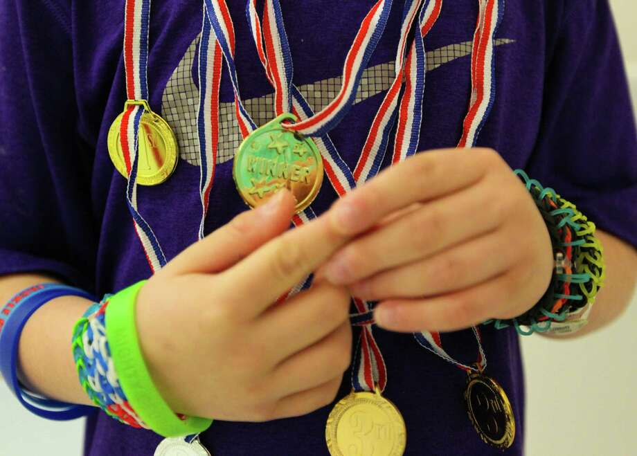 Five year-old George Gring shows off all the medals he has won during the Texas Children's Hospital Winter Olympics, Wednesday February 19, 2014 in Houston, Texas.  Texas Children's Hospital will hold their own Olympic games until February 21 giving their patients the opportunity to participate in new events for a chance to compete for the gold, silver and bronze Olympic medals. Photo: Billy Smith II, Chronicle / Houston Chronicle