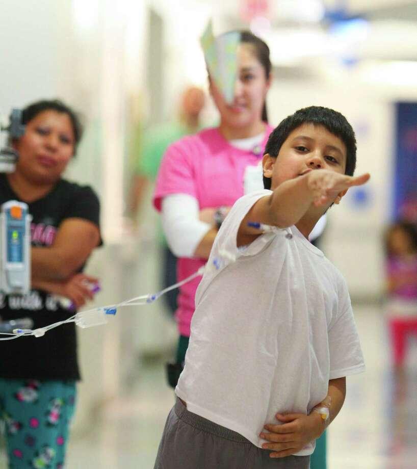 Eight year-old Leonardo Sandoval sees how long his paper plane can fly during the paper airplane challenge event in Texas Children's Hospital Winter Olympics. Photo: Billy Smith II, Chronicle / Houston Chronicle