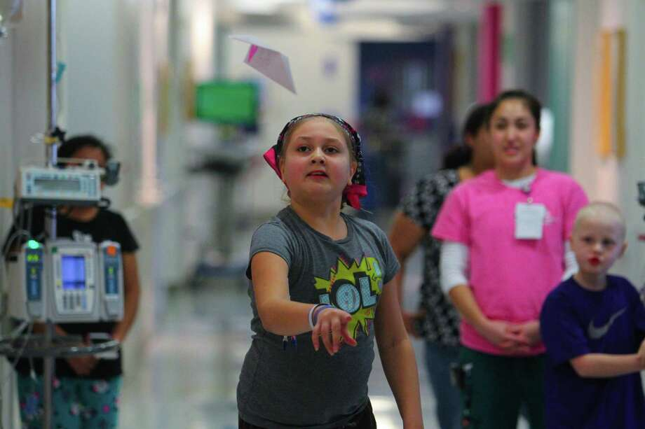 Ten year-old Emily Marroquin shows how far she can throw her paper airplane during the paper airplane challenge event in the first ever Texas Children's Hospital Winter Olympics. Photo: Billy Smith II, Chronicle / Houston Chronicle