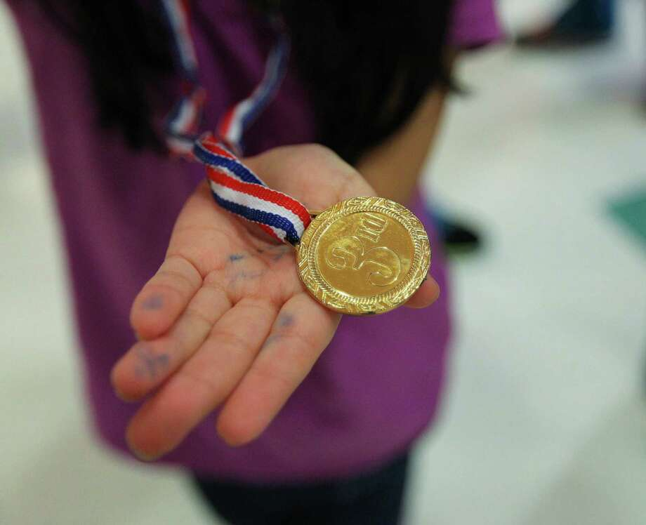 Five year-old June Isassi shows off one of the medals she won during the Texas Children's Hospital Winter Olympics. Photo: Billy Smith II, Chronicle / Houston Chronicle