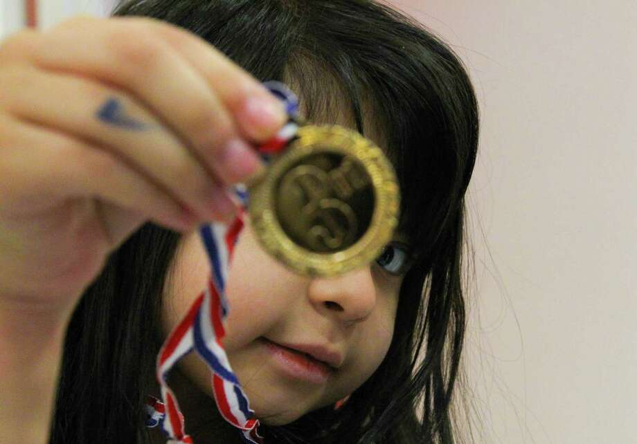 Five year-old June Isassi shows off one of her medals. Photo: Billy Smith II, Chronicle / Houston Chronicle