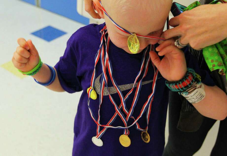 Five year-old George Gring's mom helps him put on all the medals he has won during the Texas Children's Hospital Winter Olympics. Photo: Billy Smith II, Chronicle / Houston Chronicle