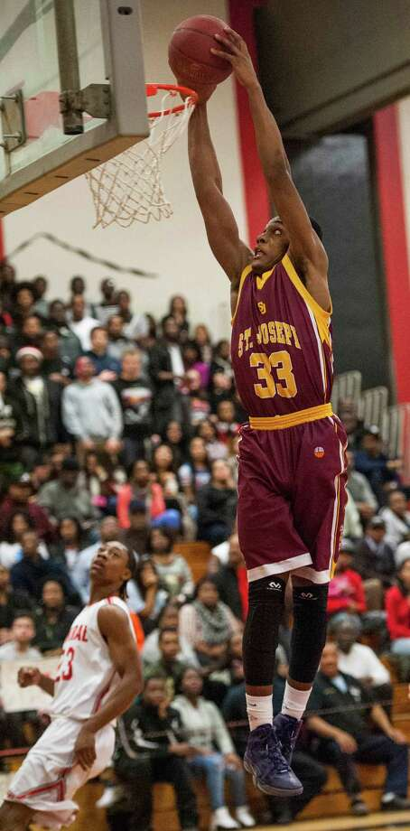 St. Joseph high school's Arkel Ager goes in for a slam dunk during a boys basketball game against Bridgeport Central high school played at Bridgeport Central high school, Bridgeport, CT on Wednesday, February, 19th, 2014. Photo: Mark Conrad / Connecticut Post Freelance