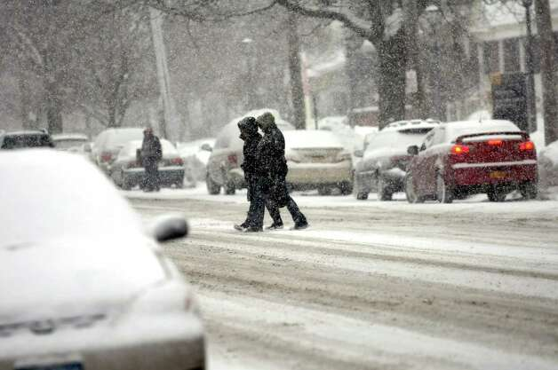 Pedestrians cross Madison Avenue during a snow squall on Wednesday, Feb. 19, 2014, in Albany, N.Y.  (Cindy Schultz / Times Union) Photo: Cindy Schultz / 00025822A