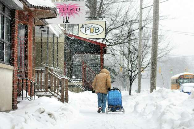 A man totes a cart along Madison Avenue during a snow squall on Wednesday, Feb. 19, 2014, in Albany, N.Y.  (Cindy Schultz / Times Union) Photo: Cindy Schultz / 00025822A