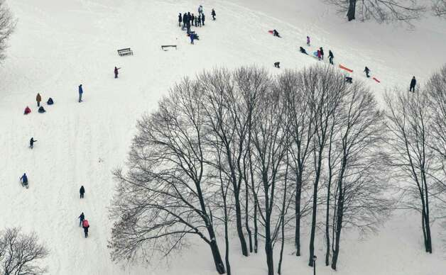 Sledders make their way down and back up a hill in Lincoln Park on Wednesday, Feb. 19, 2014 in Albany, NY.   (Paul Buckowski / Times Union) Photo: Paul Buckowski / 00025822A