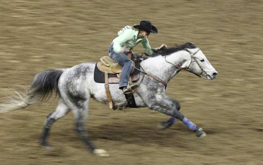 Barrel racer Christine Laughlin competes at the 2014 San Antonio Stockshow and Rodeo on Wednesday, Feb. 19, 2014. Laughlin finished with a time of 13.86. Photo: Kin Man Hui, San Antonio Express-News / ©2014 San Antonio Express-News