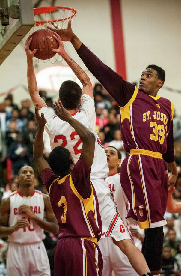 St. Joseph high school's Arkel Ager tries to block a shot by Bridgeport Central high school's Orhan Cecunjamin during a boys basketball game played at Bridgeport Central high school, Bridgeport, CT on Wednesday, February, 19th, 2014. Photo: Mark Conrad / Connecticut Post Freelance