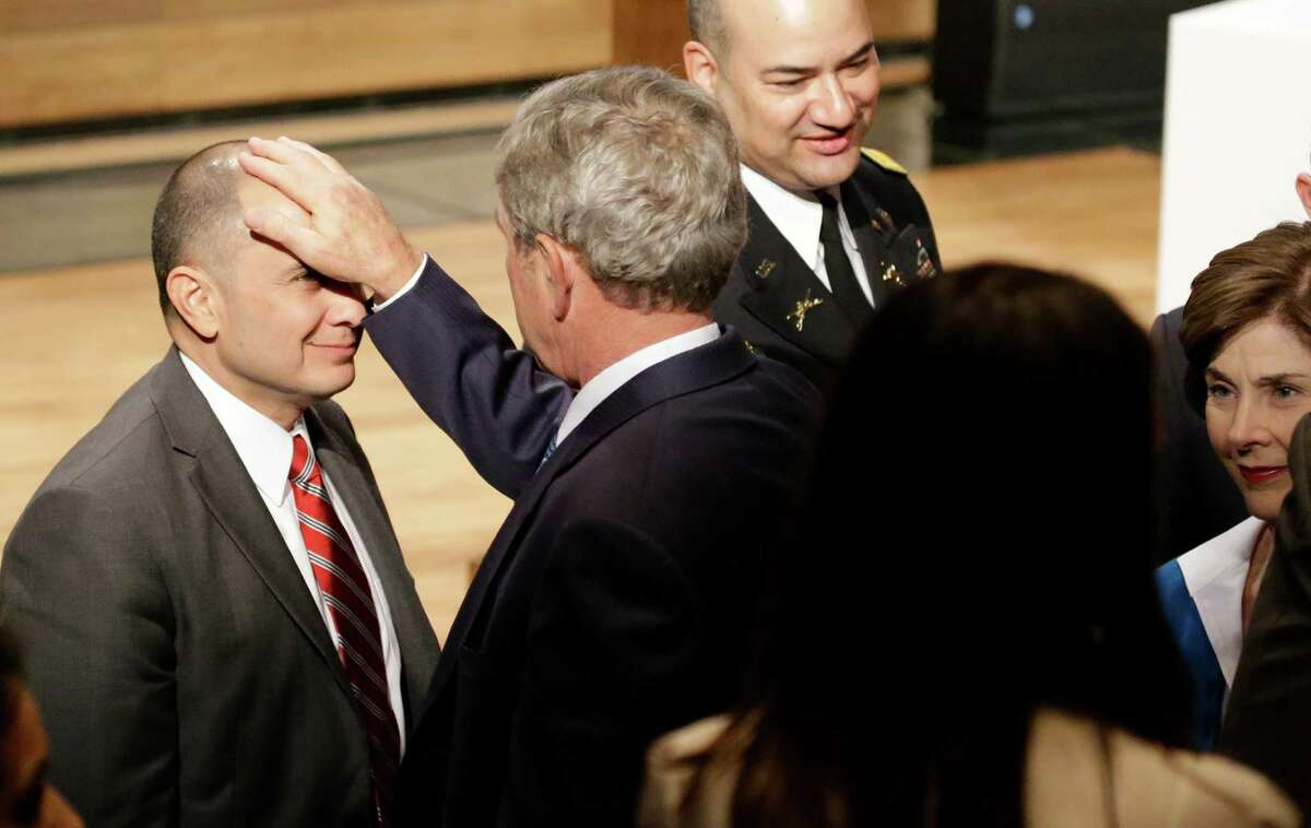 Retired Colonel Miguel Howe, left, gets a playful pat on the head from former President George W. Bush during a break in a summit titled
