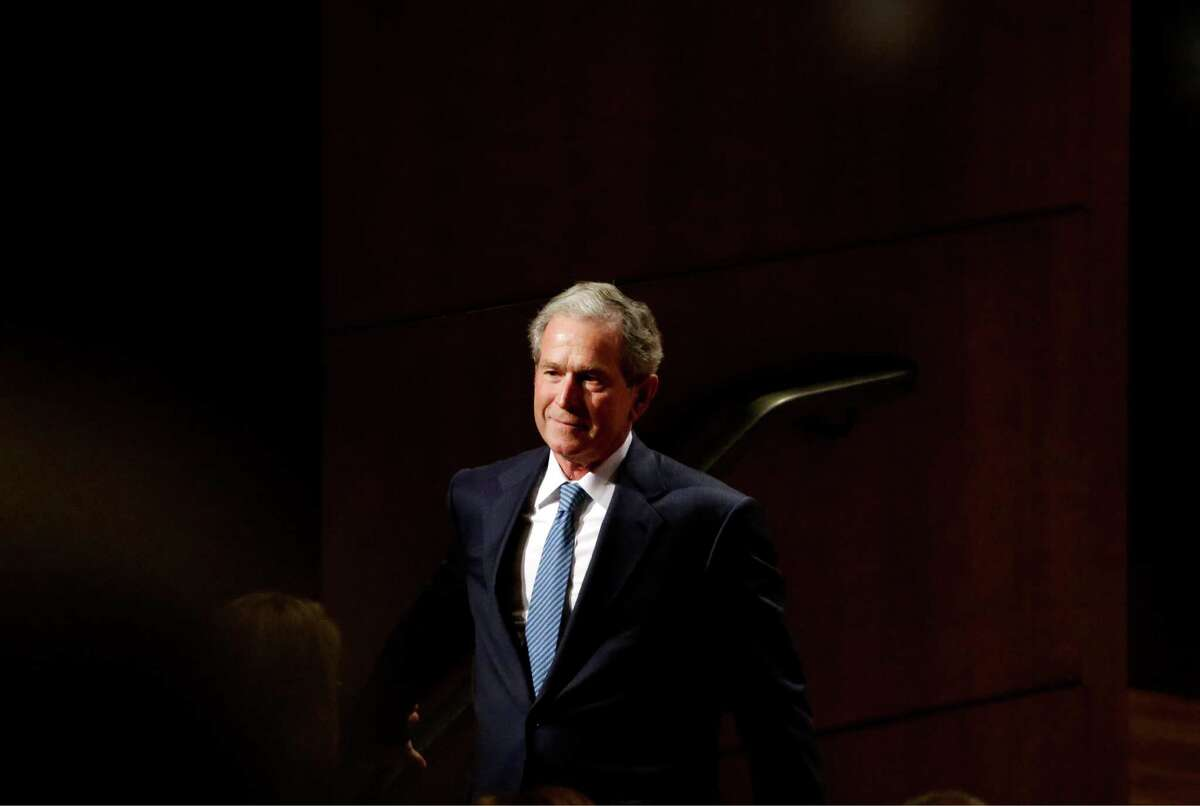 Former President George W. Bush speaks smiles as he walks off stage after giving speech at a summit titled