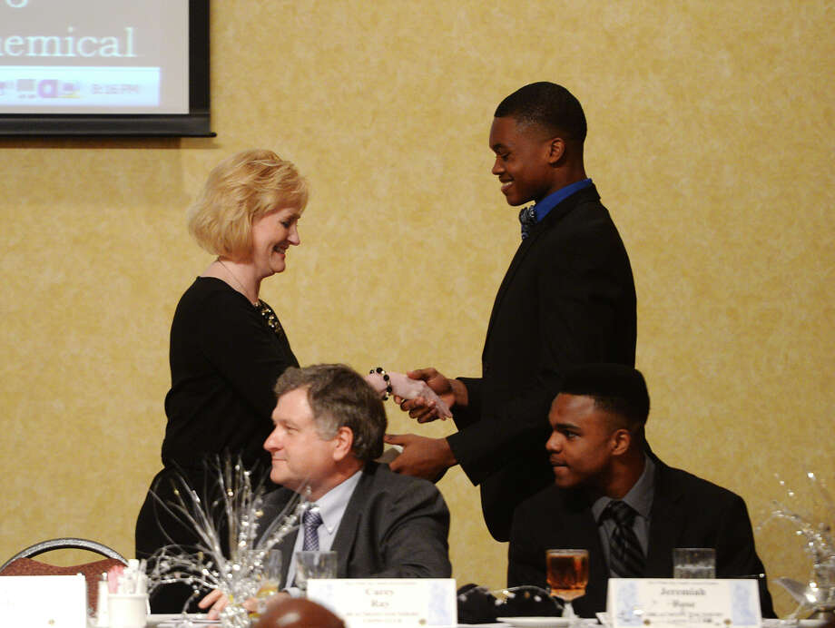 Carol Hebert of the Beaumont Lions Club presents Patrick Reed with the Willie Ray Smith award Wednesday night. The Willie Ray Smith award winners were announced during a dinner hosted by the Lions Club at the MCM Elegante on Wednesday night. Silsbee's Patrick Reed took home the honor for the offensive side, and Nederland's Deshawn Washington was chosen from the defensive player candidates. Photo taken Wednesday, 2/19/14 Jake Daniels/@JakeD_in_SETX Photo: Jake Daniels / ©2013 The Beaumont Enterprise/Jake Daniels