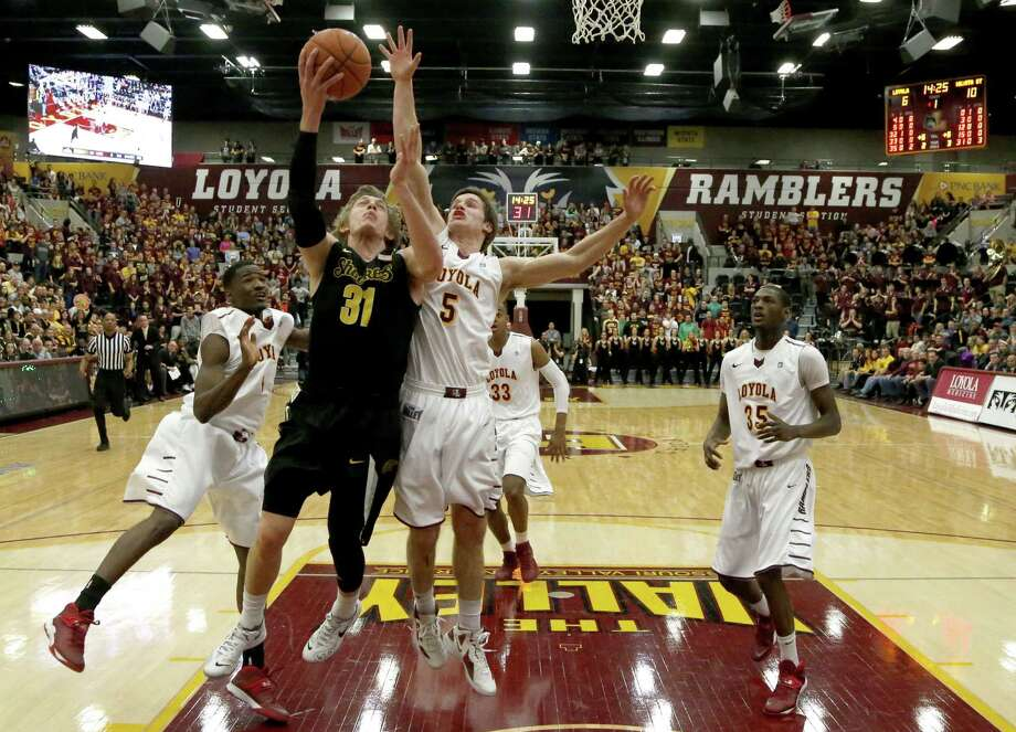 Wichita State guard Ron Baker (31) scores between Loyola of Chicago guard Devon Turk, left, and Joe Crisman (5) during the first half of an NCAA college basketball game Wednesday, Feb. 19, 2014, in Chicago. (AP Photo/Charles Rex Arbogast) ORG XMIT: ILCA106 Photo: Charles Rex Arbogast / AP