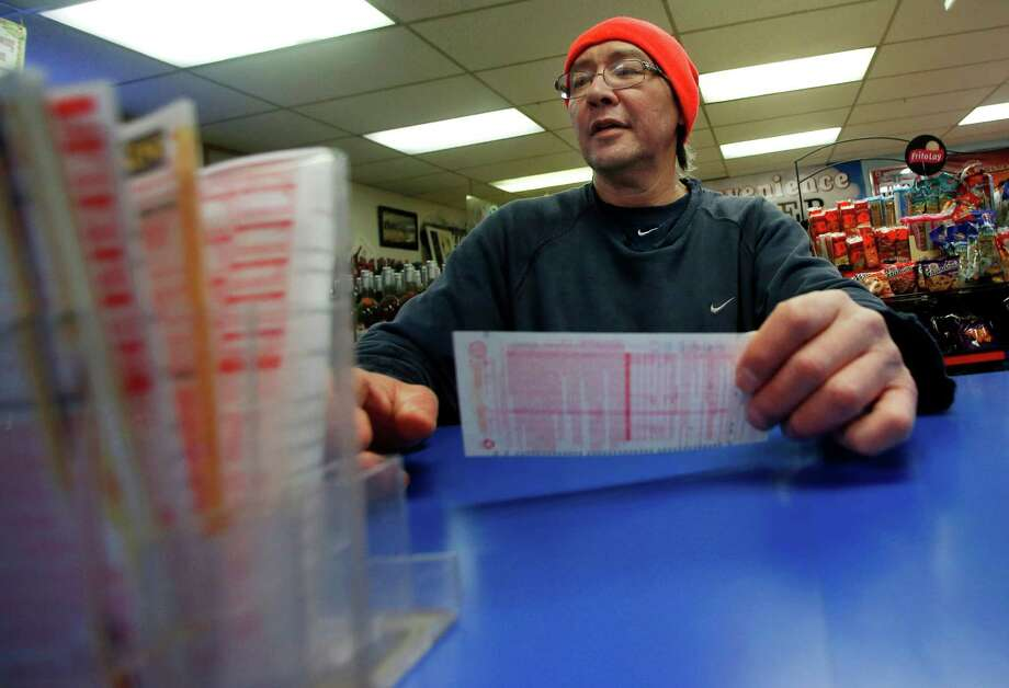 Robert Allen selects a Powerball lottery ticket to fill out at a convenience store in North Andover, Mass., Wednesday, Photo: Elise Amendola, AP / AP
