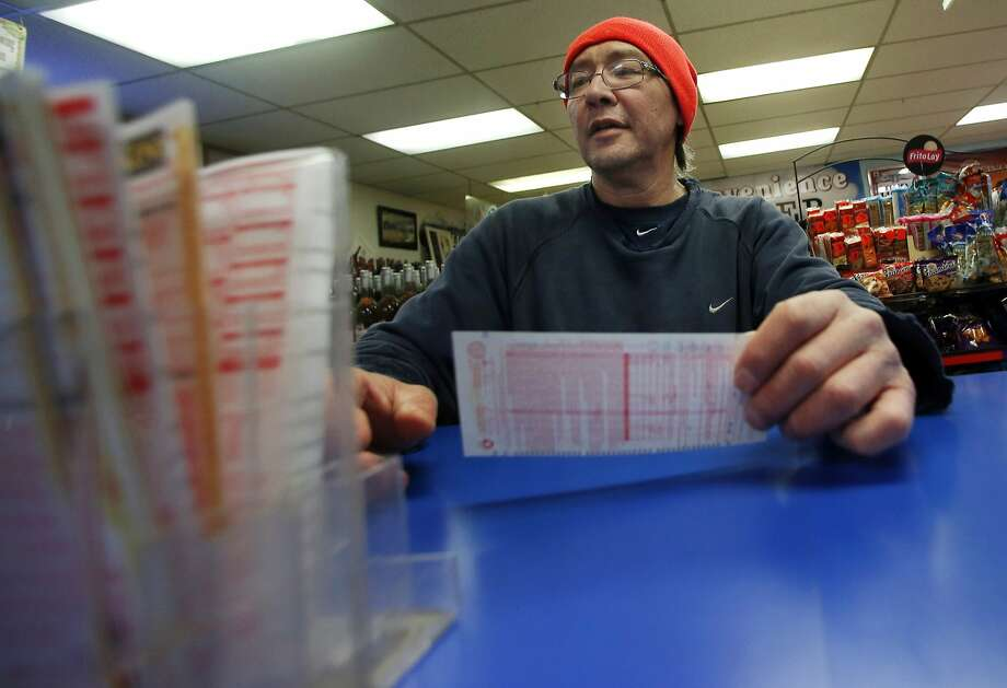 Robert Allen selects a Powerball lottery ticket to fill out at a convenience store in North Andover, Mass., Wednesday, Feb. 19, 2014. The estimated Powerball jackpot is $400 million. (AP Photo/Elise Amendola) Photo: Elise Amendola, Associated Press