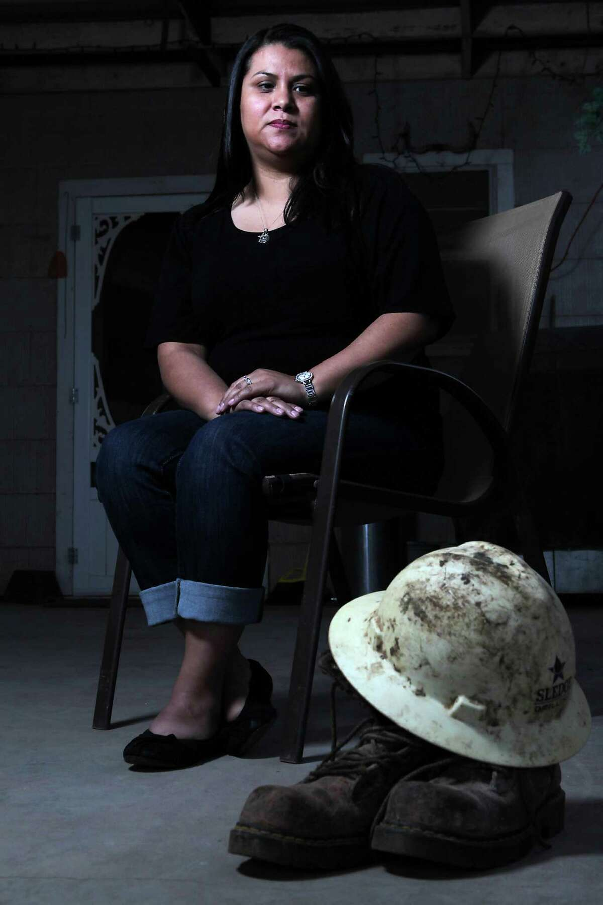 Tina Saiz, the widow of a Felipe Saiz who was killed in a drilling rig accident that occurred at Heart Land Drilling Rig 11 in June 2013, is shown with her late husband's hard hat and the boots he was wearing on the day he was killed.