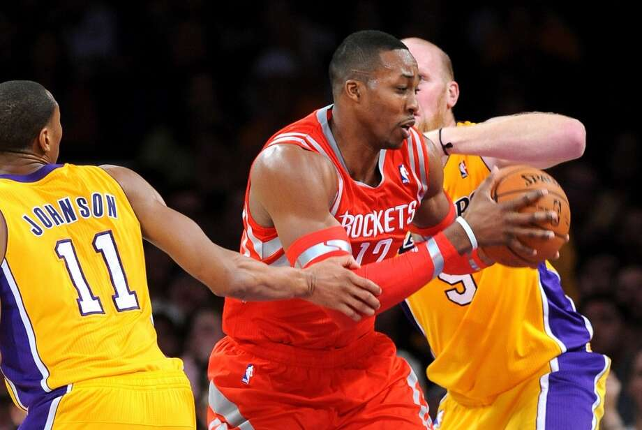 Feb. 19: Rockets 134, Lakers 108  Dwight Howard drives through Wesley Johnson (11) and Chris Kaman. Photo: Wally Skalij, McClatchy-Tribune News Service
