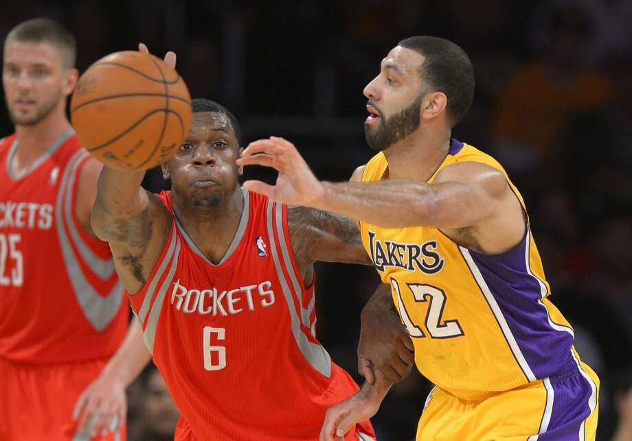 Lakers guard Kendall Marshall, right, passes the ball as Rockets forward Terrence Jones defends. Photo: Mark J. Terrill, Associated Press