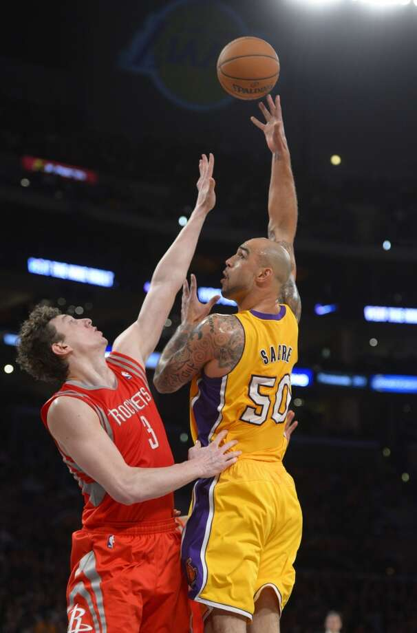 Lakers center Robert Sacre puts up a shot as Rockets center Omer Asik, of Turkey, defends. Photo: Mark J. Terrill, Associated Press