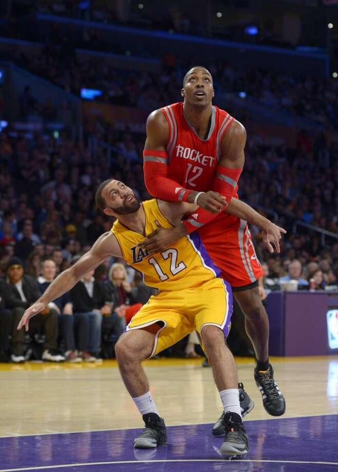 Rockets center Dwight Howard, right, battles for a rebound with Lakers guard Kendall Marshall. Photo: Mark J. Terrill, Associated Press