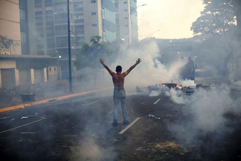 A demonstrator raises his arms toward the Bolivarian National Police (BNP) firing tear gas and a water canon in the Altamira neighborhood of Caracas, Venezuela, Wednesday, Feb. 19, 2014. The opposition is protesting the Tuesday detention of their leader Leopoldo Lopez, as well as rampant crime, shortages of consumer goods and an inflation rate of more than 50 percent.  (AP Photo/Rodrigo Abd) Photo: Rodrigo Abd, Associated Press