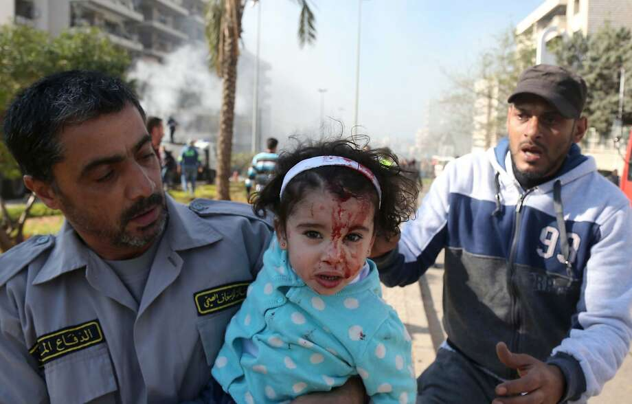 TOPSHOTS Lebanese emergency personnel evacuate an injured girl from an orphanage located next to the site of a bomb explosion in a southern suburb of the capital Beirut on February 19, 2014. Twin bomb blasts appeared to target the Iranian cultural centre, and an AFP photographer at the scene said the blasts had occurred beyond a security checkpoint at the centre, close to the building. AFP PHOTO / STR-/AFP/Getty Images Photo: -, AFP/Getty Images