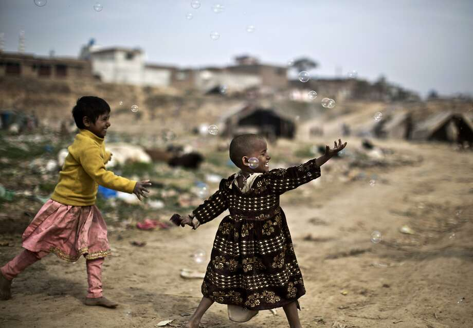 Pakistani girls chase bubbles released by a vendor, in a slum in Rawalpindi, Pakistan, Wednesday, Feb. 19, 2014. (AP Photo/Muhammed Muheisen) Photo: Muhammed Muheisen, Associated Press