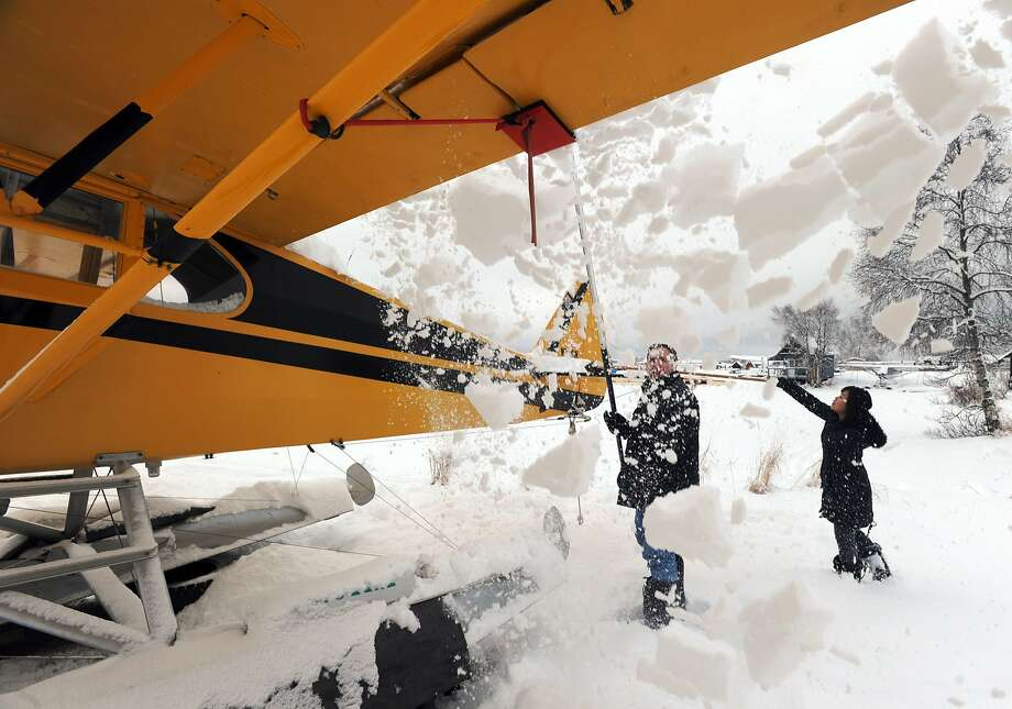 What friends are for - snow removal:Craig Lee and his wife, Karen, brush snow off a friend's plane at Lake Hood Seaplane Base 