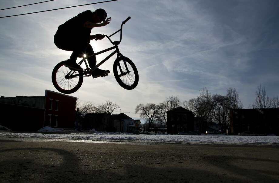 Elijah Rushinsky does a trick on his bicycle Wednesday, Feb. 19, 2014, in Lafayette, Ind. National Weather Service meteorologists say temperatures that could hit the 50s and 60s on Thursday also could bring two other spring like hazards: high winds and flooding. (AP Photo/The Journal & Courier, Michael Heinz) Photo: Michael Heinz, Associated Press