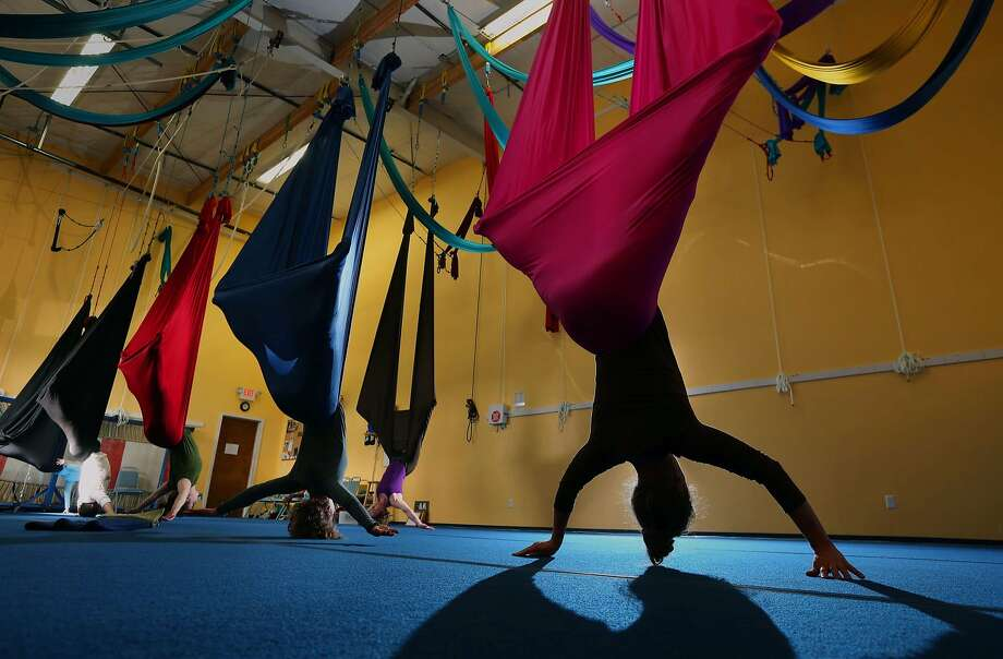 Amber Rene Lippel, right, hangs from a colorful bolt of fabric as she joins an aerial yoga class lead by Naja Rossoff owner, background center, of Bounce Gymnastics in Eugene, Ore. Wednesday, Feb. 19, 2014. The class, which combines aspects of yoga and and aerial silks, is offered in the evenings Monday and Tuesday and in the mornings Wednesday and Thursday. (AP Photo/The Register-Guard, Chris Pietsch) Photo: Chris PIetsch, Associated Press