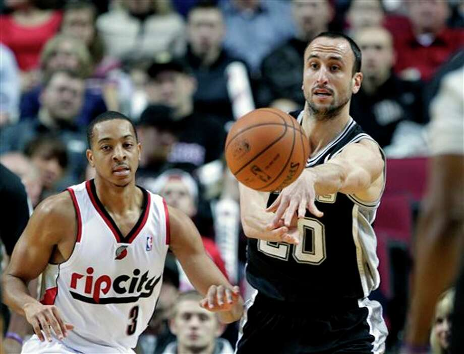 San Antonio Spurs guard Manu Ginobli, from Argentina, right, passes off as Portland Trail Blazers guard CJ McCollum defends during the first half of an NBA basketball game in Portland, Ore., Wednesday, Feb. 19, 2014.(AP Photo/Don Ryan) Photo: Don Ryan, AP / AP