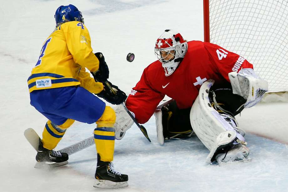 Goalkeeper Florence Schelling of Switzerland (41) blocks Jenni Asserholt of Sweden's (4) shot on the goal during the second period of the women's bronze medal ice hockey game at the 2014 Winter Olympics, Thursday, Feb. 20, 2014, in Sochi, Russia.  Photo: Julio Cortez, Associated Press