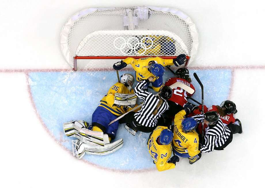Referees intervene as Swiss and Swedish players pile into the net of Valentina Lizana Wallner #35 of Sweden during the Ice Hockey Women's Bronze Medal Game on day 13 of the Sochi 2014 Winter Olympics at Bolshoy Ice Dome on February 20, 2014 in Sochi, Russia. Photo: Martin Rose, Getty Images