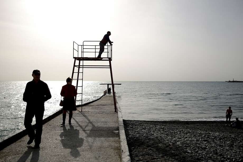 People walk along the Black Sea at the 2014 Winter Olympics, Thursday, Feb. 20, 2014, in Sochi, Russia. Photo: Jae C. Hong, Associated Press
