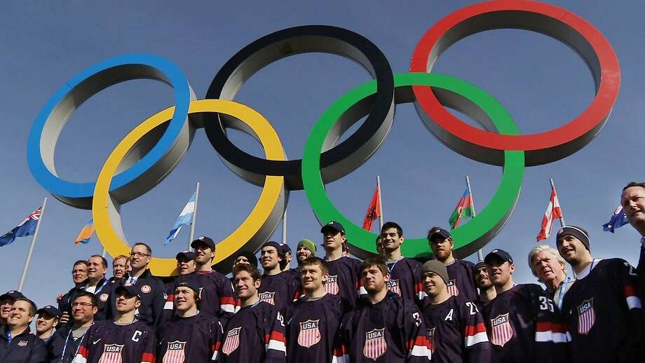 In this still image taken from video, members of the men's ice hockey team from the United States post in front of the Olympic rings in Olympic Park during the 2014 Winter Olympics in Sochi, Russia, on Thursday, Feb. 20, 2014. The U.S. and Canada will play each other in the semifinal round on Friday, Feb. 21.  Photo: Ben Jary, Associated Press