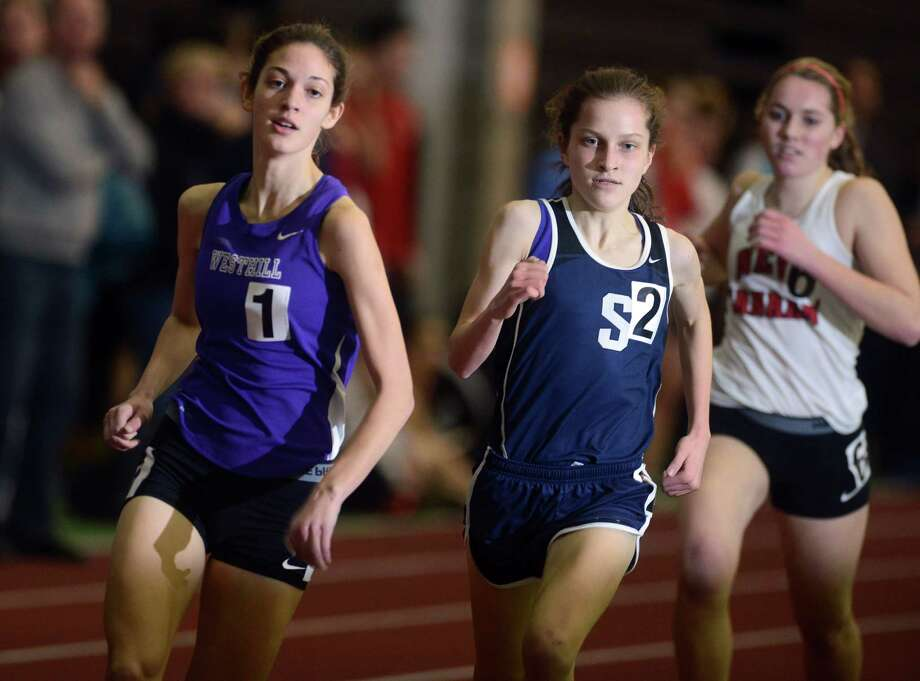 Westhill's Claire Howlett, left, and Staples' Hannah DeBalsi keep pace during the 1600 meter run at the FCIAC Indoor Track Championships Wednesday, Jan. 29, 2014, at the Floyd Little Athletic Center in New Haven, Conn. Photo: Autumn Driscoll / Connecticut Post
