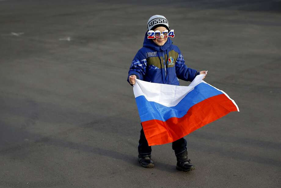 A boy carries a Russian national flag as he walks through Olympic Park at the 2014 Winter Olympics in Sochi, Russia, Thursday, Feb. 20, 2014. Photo: Patrick Semansky, Associated Press