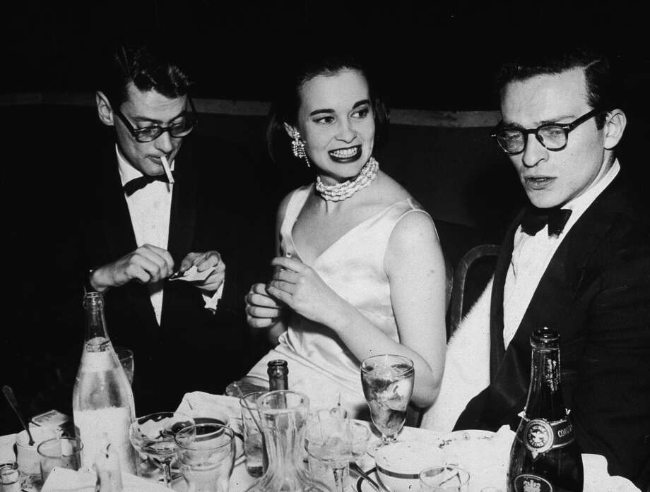 "American photographer Richard Avedon (left, lighting a cigarette), American heiress and designer Gloria Vanderbilt, and American film director Sidney Lumet, sit at a table covered with glasses and bottles during a party for the premiere of the movie ""East of Eden'""directed by Elia Kazan, 1955. Photo: Hulton Archive, Getty Images"