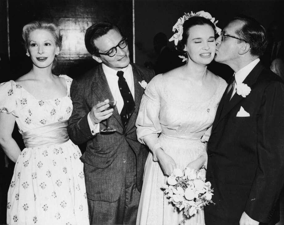 Blacklisted American playwright Sidney Kingsley (far left) kisses the cheek of Gloria Vanderbilt as American film director Sidney Lumet and American actress Carol Grace stand by during Lumet and Vanderbilt's wedding, August 28, 1956. Photo: Hulton Archive, Getty Images