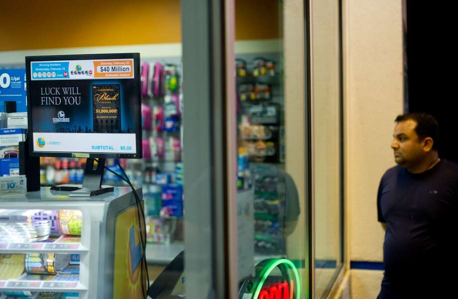 An unidentified customer looks at a screen displaying the winning Powerball numbers at Dixon Landing Chevron in Milpitas on Thursday.  According to California lottery officials, the store sold the lone winning ticket for a $425 million Powerball jackpot but there was no immediate word on who may have won one of the largest lottery jackpots in U.S. history. Photo: Noah Berger, Associated Press