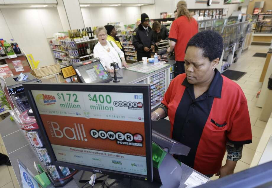Convenience  store employee, Velda Venable, of Richmond, operates a lottery machine in Richmond, Va., Wednesday, Feb. 19, 2014. The estimated Powerball lottery jackpot is $425 million. Photo: Steve Helber, Associated Press
