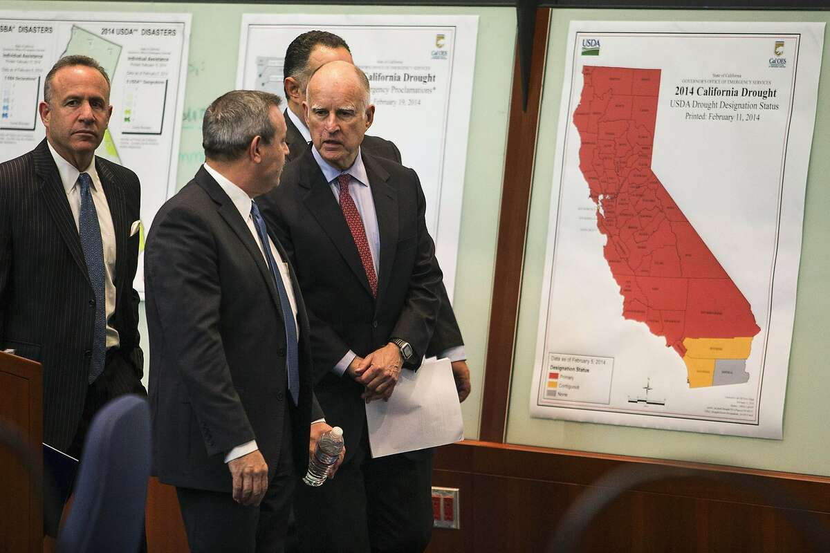 Director of Emergency Services Mark Ghilarducci (second from left) gives California Governor Jerry Brown a tour of the Cal OES State Operations Center in Mather, California, February 19, 2014. Brown announced a $687 million drought-relief package to help residents, farm workers and local communities cope with a water shortage he called the worst in the state's modern history. Brown, joined in Sacramento by top Democratic state lawmakers, told a news conference the money would provide food and housing aid to those who have lost work because of the drought and expedite funding to state and local water conservation and reuse projects.