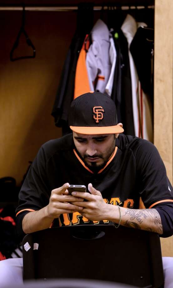 Giants' pitcher Sergio Romo,(54) keeps watch on his messages in the clubhouse before the start of practice in Scottsdale, Arizona on Wednesday Feb. 19, 2014. The San Francisco Giants continue their spring training schedule in the Arizona desert with the full squad taking to the practice fields at Scottsdale Stadium. Photo: The Chronicle