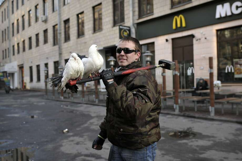 Mixed metaphor:Doves perch on a protester's hammer in central Kiev. Photo: Louisa Gouliamaki, AFP/Getty Images