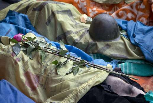 Flowers are laid on an Ukrainian flag covering body of a killed anti-government protester, in central Kiev, Ukraine, Thursday, Feb. 20, 2014. A brief truce in Ukraine's embattled capital failed Thursday, spiraling into fierce clashes between police and anti-government protesters. (AP Photo/Darko Bandic) Photo: Darko Bandic, Associated Press