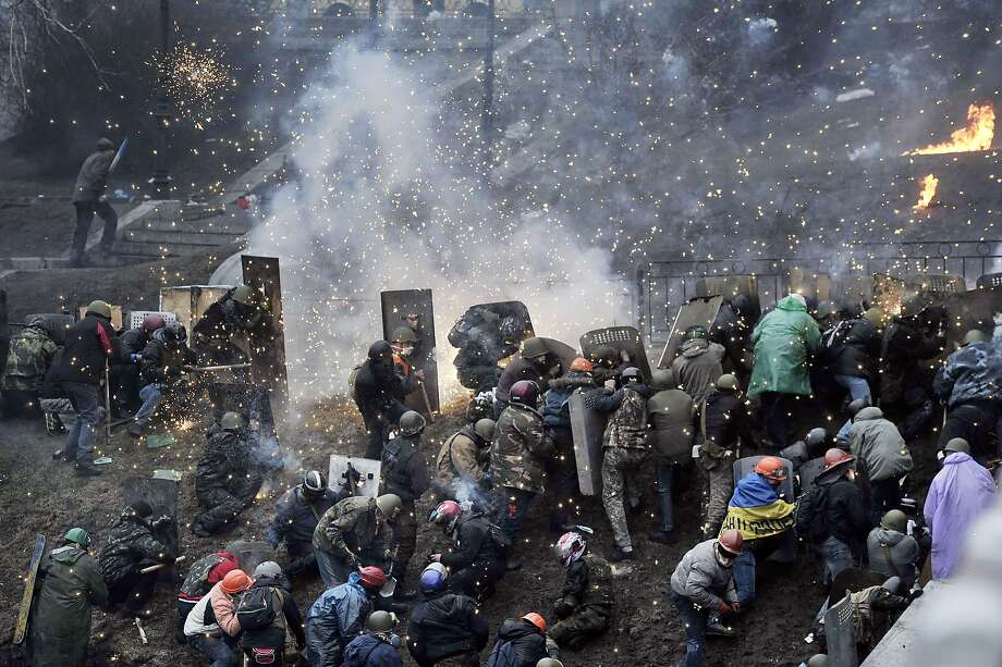 Carnage in Kiev:Protesters clash with police after gaining ground near Independence Square. Armed protesters charged police barricades despite a truce called just 