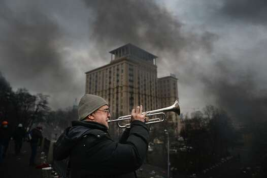 KIEV, UKRAINE - FEBRUARY 20:  A man plays the trumpet as anti-government protesters continue to clash with police in Independence square, despite a truce agreed between the Ukrainian president and opposition leaders on February 20, 2014 in Kiev, Ukraine. After several weeks of calm, violence has again flared between police and anti-government protesters, who are calling to oust President Viktor Yanukovych over corruption and an abandoned trade agreement with the European Union.  (Photo by Jeff J Mitchell/Getty Images) Photo: Jeff J Mitchell, Getty Images